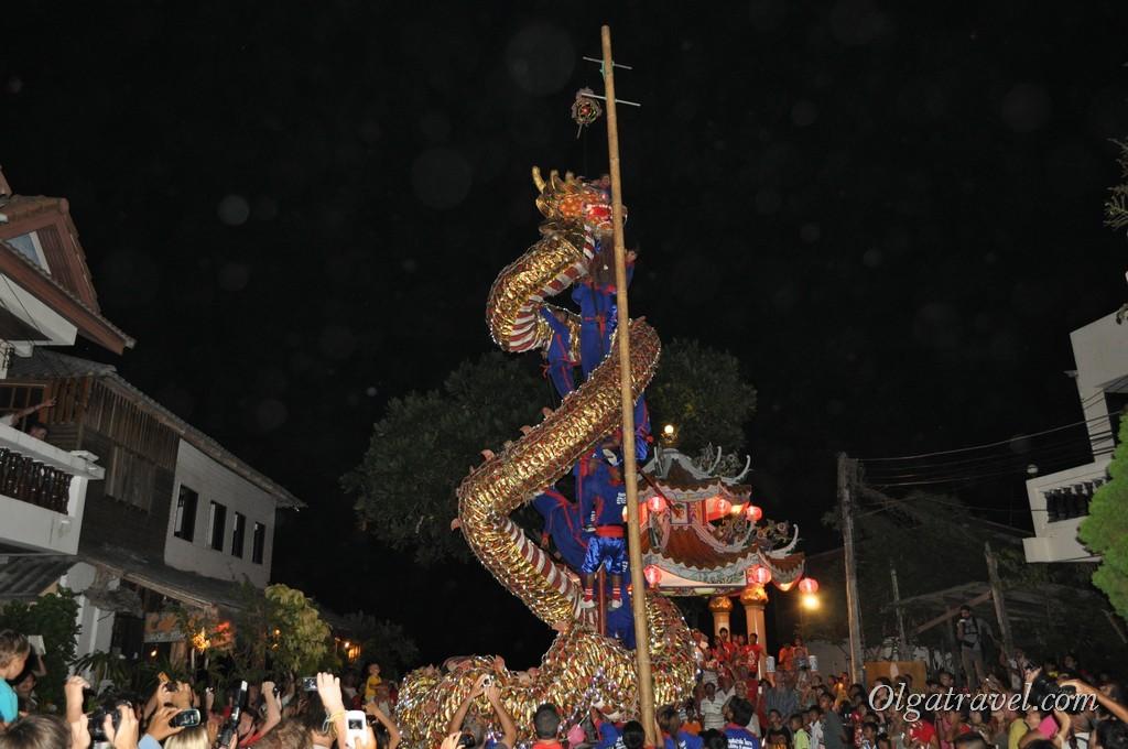 Люди залезли на высокий шест и стали закручивать на него дракона