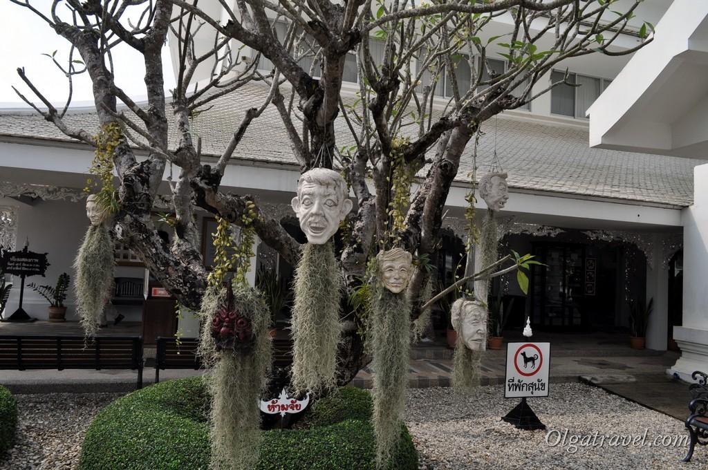 Смеющиеся маски на деревьях