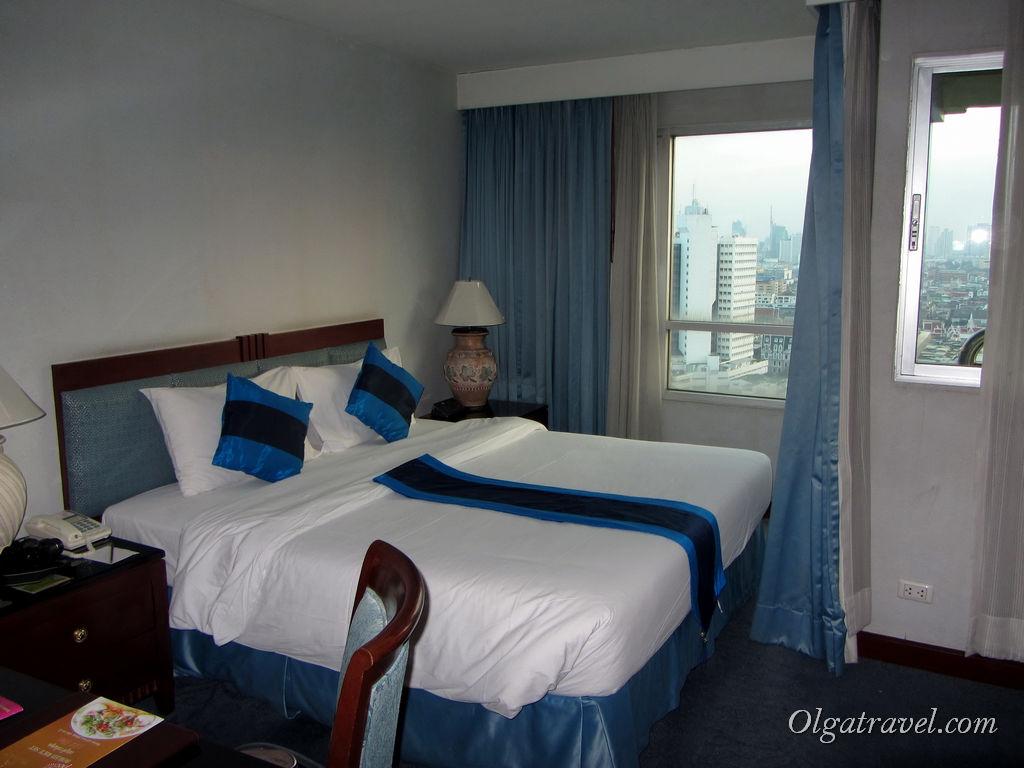 Отельная спальня с большой кроватью и удобным письменным столом для работы